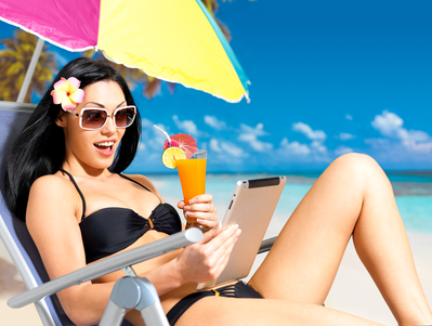 Happy woman on the beach with ipad. Vacation and communication concept.